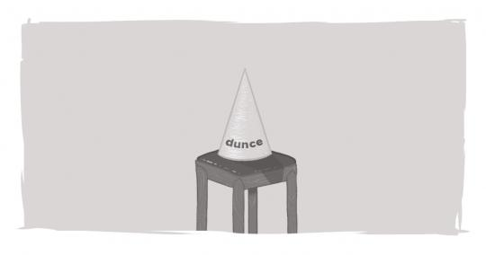 A dunce cap sitting on an empty chair.