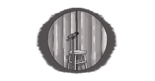 An image of an empty microphone, spotlighted on a stage.