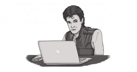 An image of Rick Springfield, singer of Human Touch, behind a laptop.